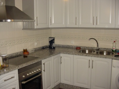 La cocina con encimera y fregadero